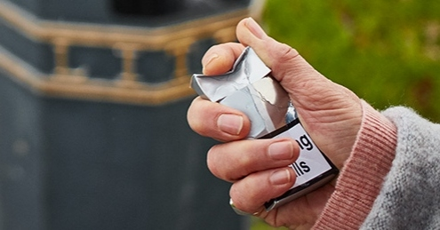 A hand crushing a packet of cigarettes